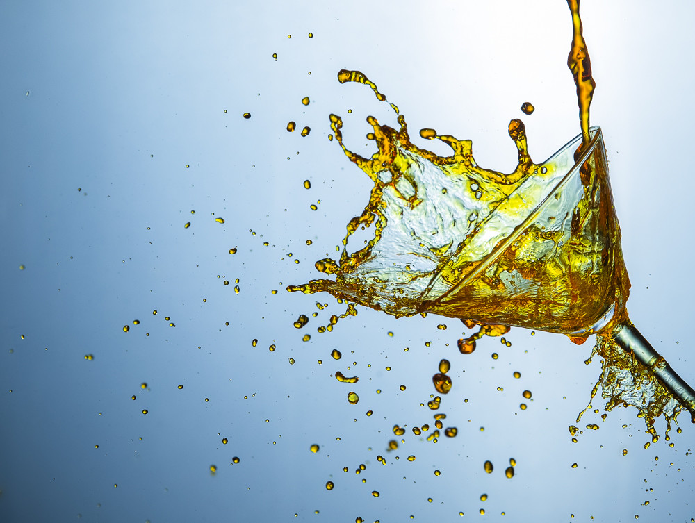 High Speed Liquids Photography. Plenty of Alcohol Drink Little Droplets Poured Out of The Clear Wine Glass.