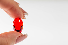 The woman is holding a red capsule painkiller