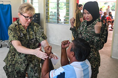 U.S. Navy Cmdr. Cyndi Sikorski, left, and Malaysian Army Cpl. Norazimah Halidi conduct stimulation exercises with a participant during a community health engagement in Kuching. (U.S. Navy/MC2 Nicholas Burgains)
