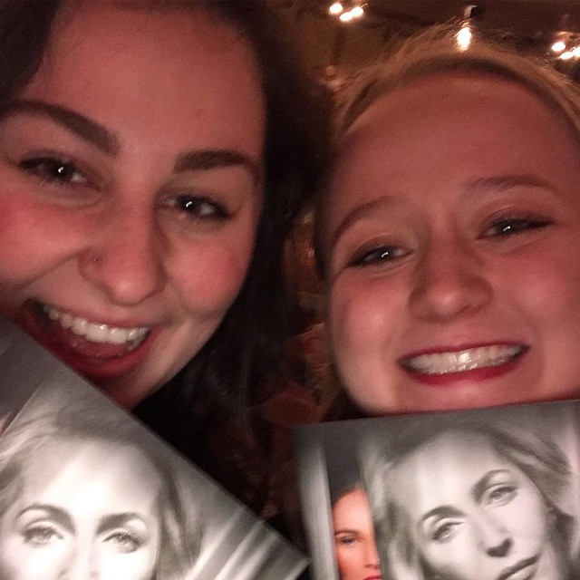 Two girls holding up playbills of with a woman's face on them.