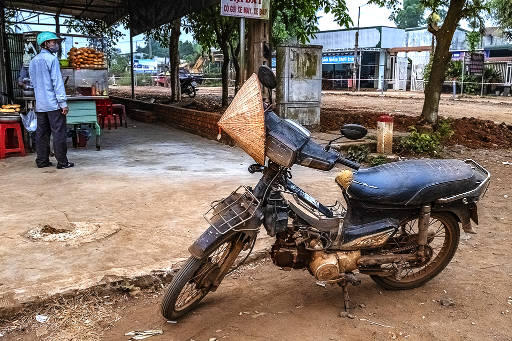 Beat up motorbike with conical hat--Ea Kly