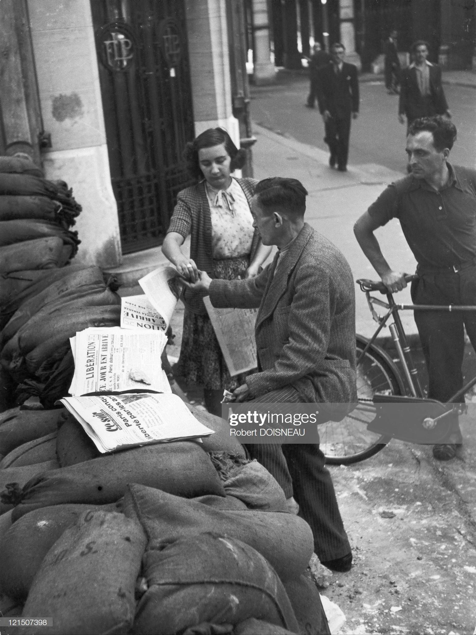 1944. Некоторым продавцам парижских газет больше не нужно прятаться от немцев и они выполняют свою работу на баррикадах