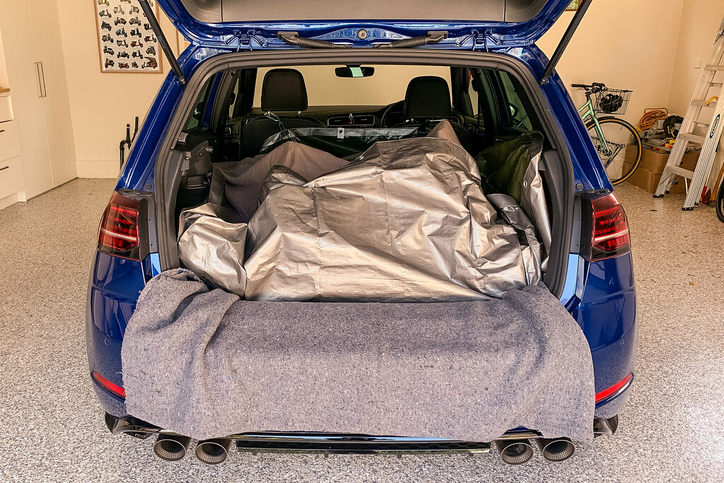 Blue hatchback with hatch open and mountain bike covered with a tarp