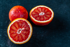 Whole and two halves of red orange on dark background