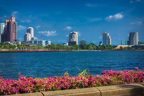 Benjakiti lake with skyline and Bougainvilleas in Bangkok, Thailand