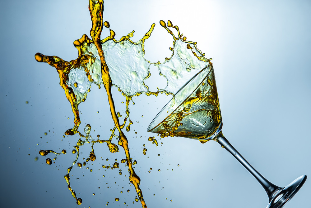 High Speed Liquids Photography. Alcohol Drink Droplets Poured Out of The Clear Wine Glass.