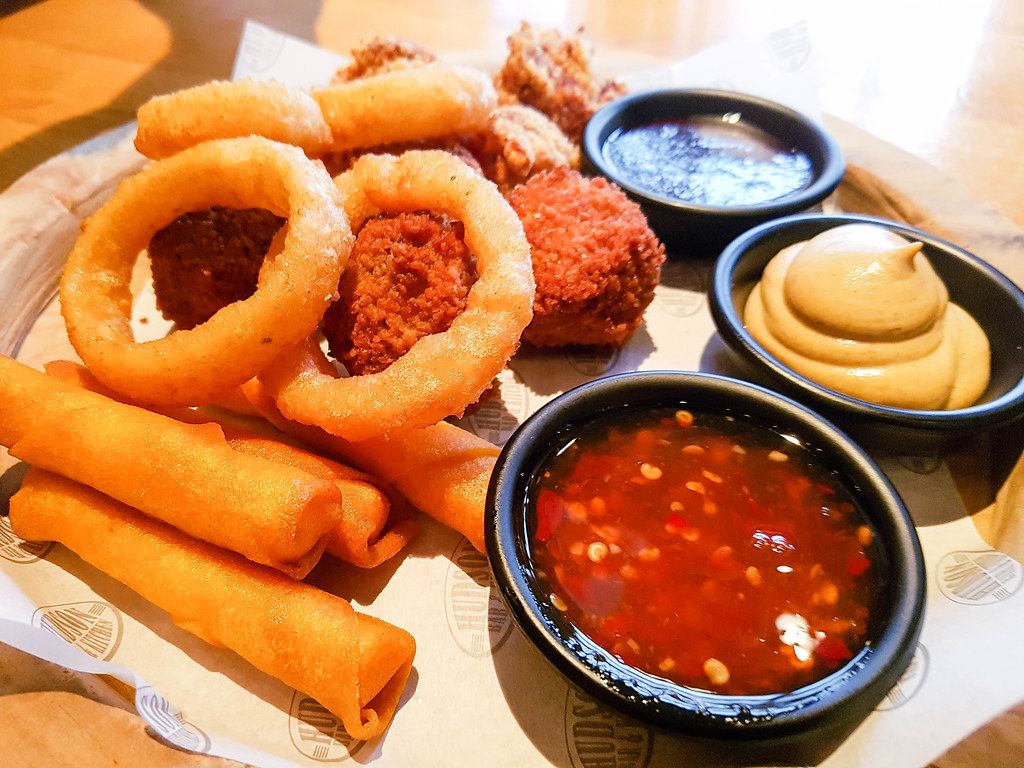 A platter of different snacks such as spring rolls, onion rings and bitterballen, with dips