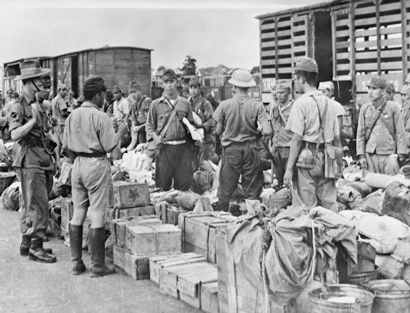 A British officer of a Gurkha battalion gives the order, through an interpreter, for Japanese prisoners to hand over all sharp objects such as knives, needles and razors before boarding trains that will carry them to prisoner of war camps outside the city of Bangkok, September 1945.