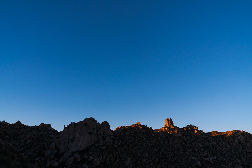 A distant view of Tom's Thumb as the first light of sunrise falls upon it in McDowell Sonoran Preserve in Scottsdale, Arizona