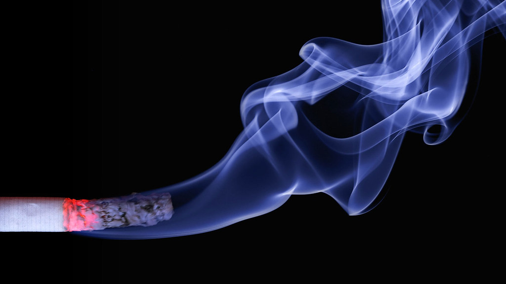 A lit cigarette with smoke coming out of it
