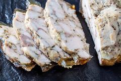Sliced homemade ham on black stone background