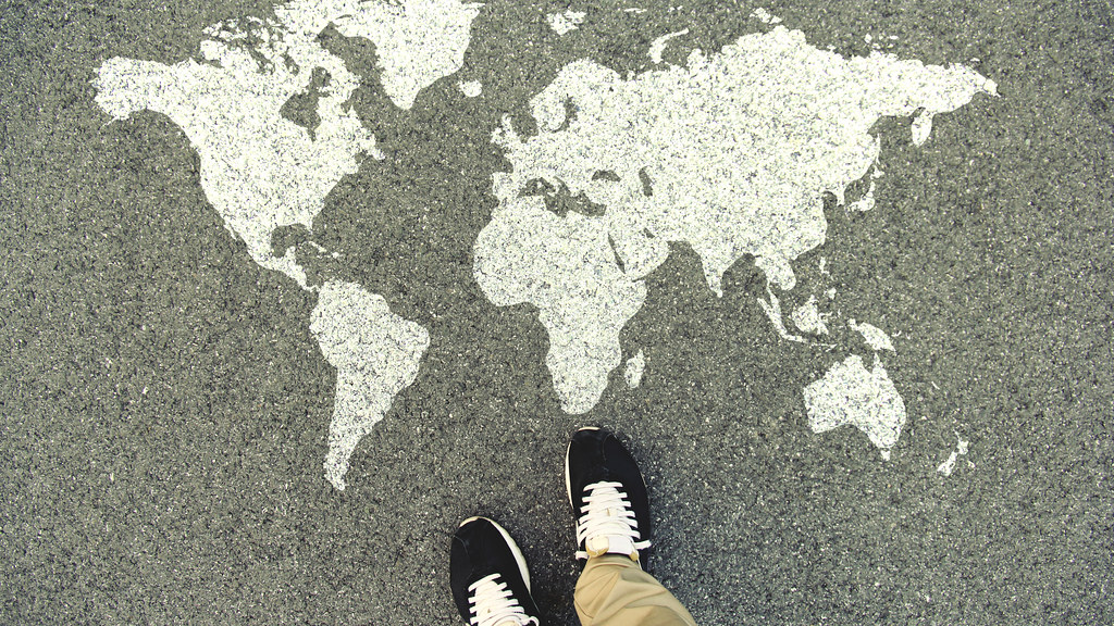 A map of the world painted on the ground with a view of a persons shoes