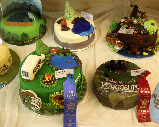 5 double-layer round cakes decorated with park themes, such as Voyageurs National Park or camping.