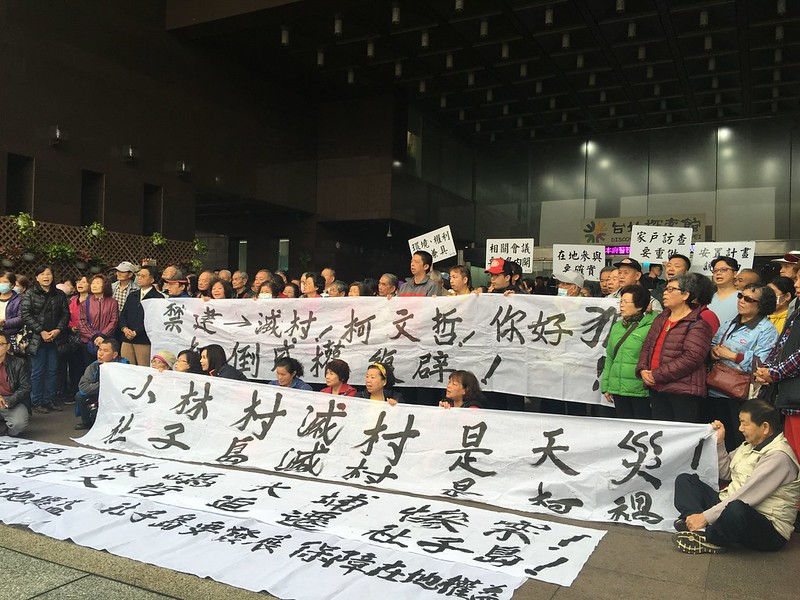 社子島居民在市政府前喊口號抗議,拉出「社子島滅村是柯禍」布條。環境權保障基金會提供。
