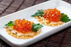 Sandwiches with salmon caviar and cheese on a white plate