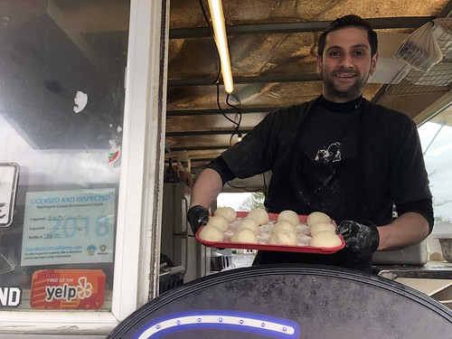 Mario with tray of pita dough. From Interested in Lebanese Cuisine? Here's What to Expect–and Try!