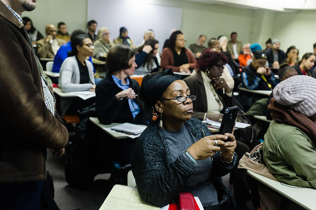 Photo of adults in school desks facing the facing the same direction at attention. One woman is filming the presentation on her cell phone.
