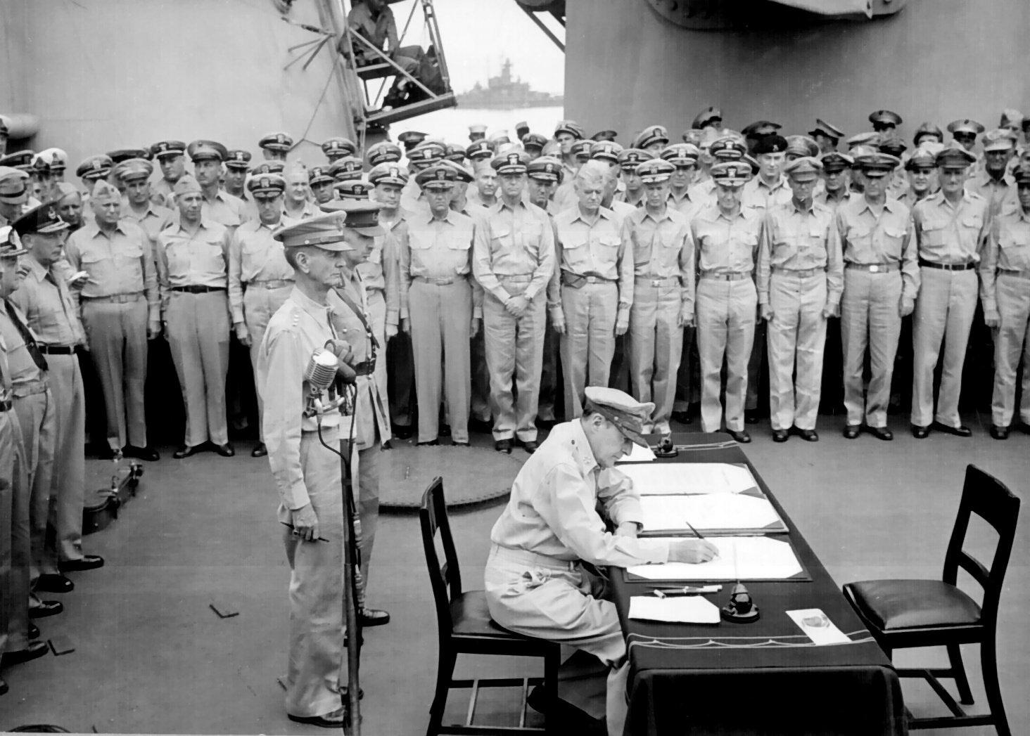 General Douglas MacArthur signs Japanese surrender instrument as Supreme Allied Commander during formal surrender ceremonies on the USS Missouri in Tokyo Bay on September 2, 1945. Behind General MacArthur are U.S. Lieutenant General Jonathan Wainwright and British Lieutenant General Arthur E. Percival.