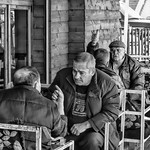Tiranian men engage in intense discussions while drinking `birra` aka beer.