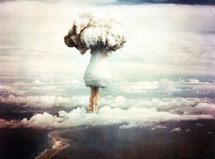 A mushroom cloud rises into a cloudy sky.