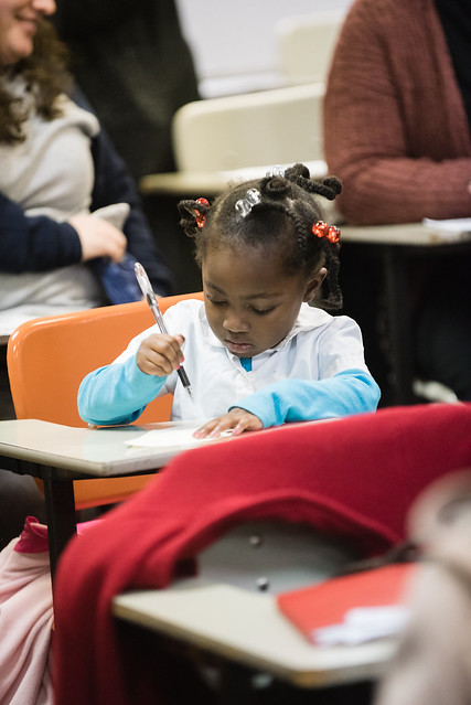 Photo of a child sitting in a school desk, surrounded by adults sitting in school desks, picking up a pen and looking at a sheet of paper.