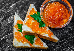 Red caviar in a glass bowl and on sandwiches on a black stone background