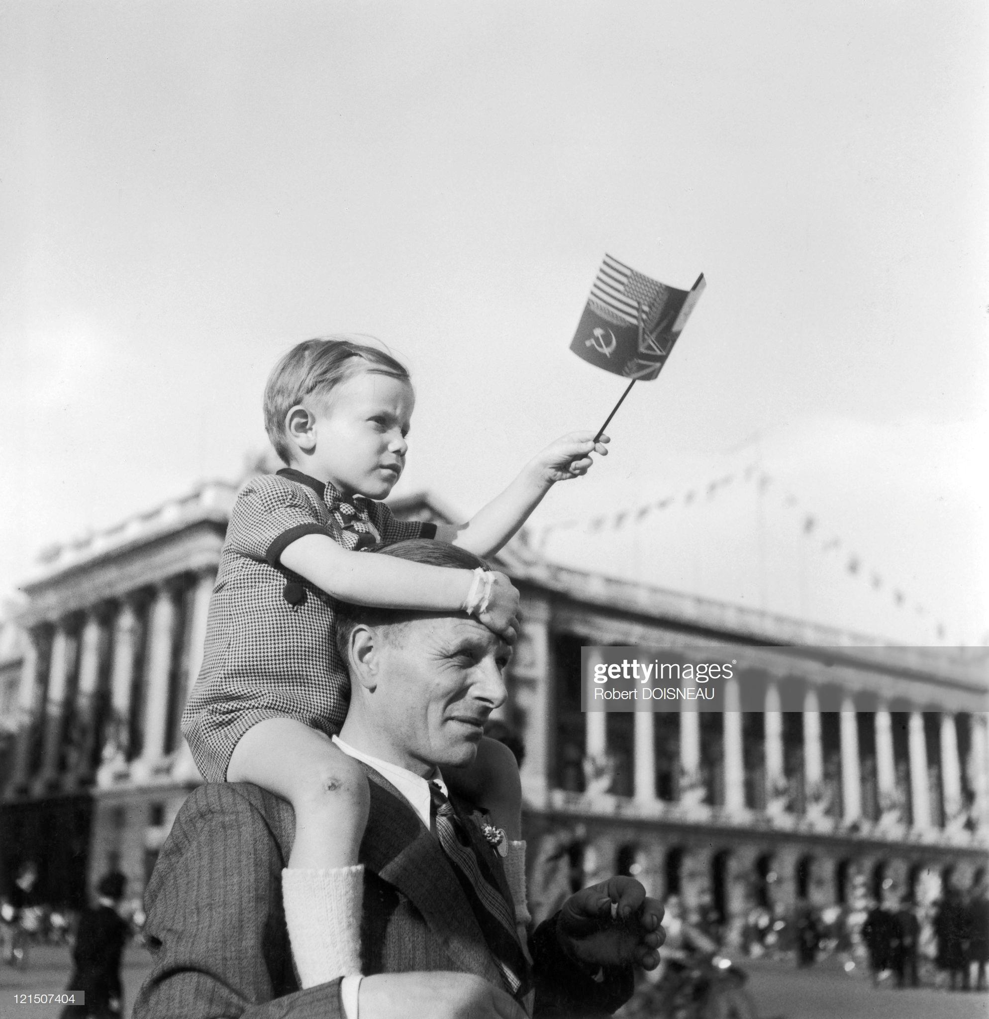 1944. Мальчик сидит на плечах своего отца и держит флажок с изображением флагов союзников во время парада на площади Согласия