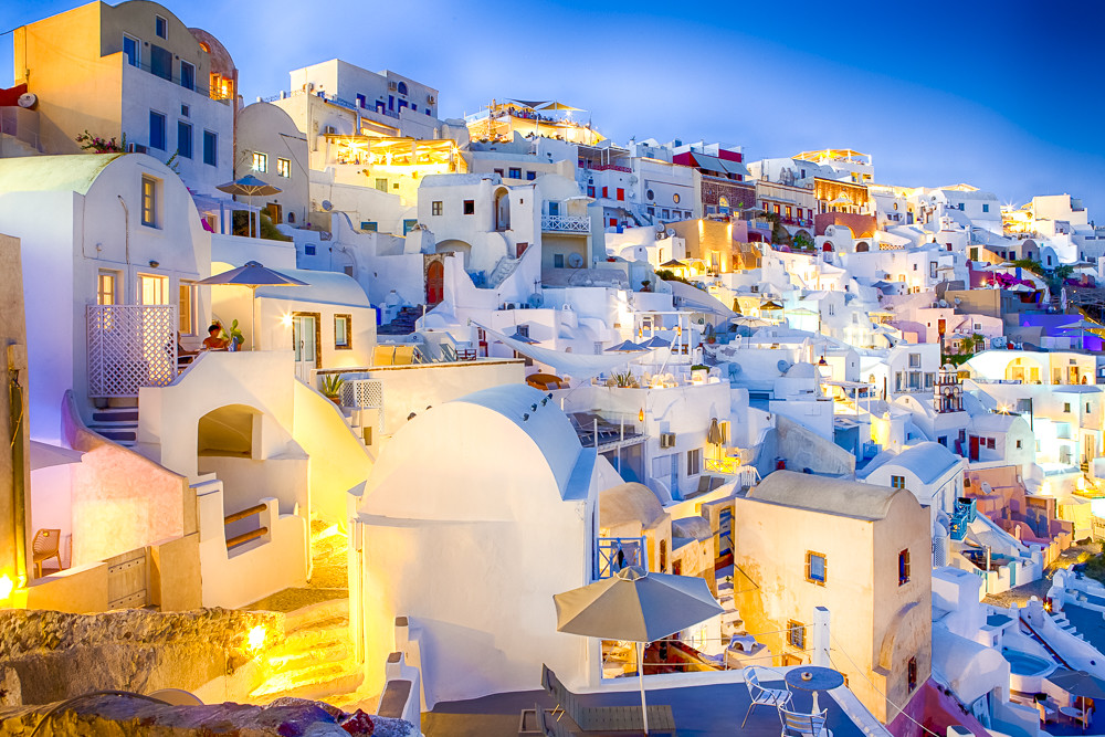 Romantic Destinations. Unique Picturesque Citiscape panorama of Oia Village Located on Volcanic Caldera Hills on Santorini Island Before The Sunset