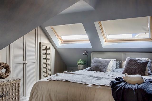 Landelijke slaapkamer met schuine wand en dakramen