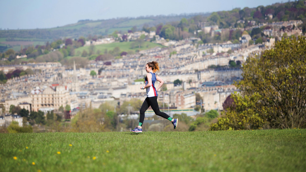 A runner on the Bath Skyline route with the city behind them