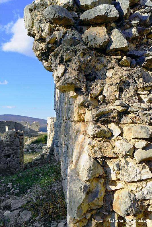 Разрушенная каменная стена на верхнем уровне крепости