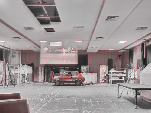 Fiat at the Rehearsal Room - under the car not a car mechanic, but the set designer assistant. Operation Zinnober - Auto (roter Fiat Polski) im Probenraum - von meinem Platz aus gesehen, Auf der Leinwand Livevideo