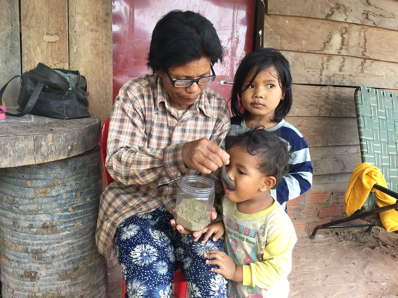 Phally Siev feeds her three-year-old grandchild a powder made from nutritious small fish. Photo by Mith Samonn.