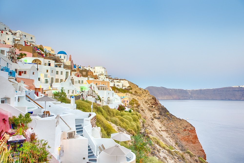 Romantic Destination. Picturesque Cityscape of Oia Village on Santorini Island with Caldera Mountains On Background in Rays of Setting Sun.