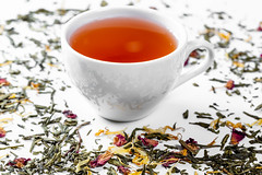 Dried tea with petals and a Cup of fresh tea