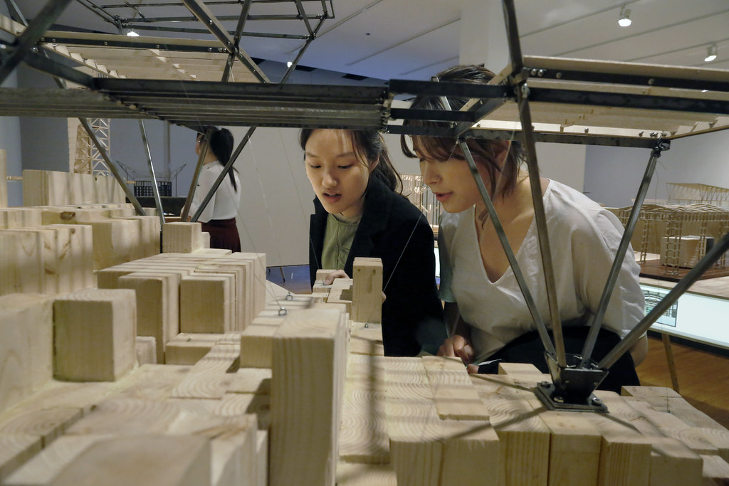 Jaein Lee (B.Arch. '22), left, and Kaylin Park (B.Arch. '19) discuss Lee's model of the V House by Heinz Legler, in the exhibition <em>Structural Systems Class Models, Fall 2018,</em> in John Hartell Gallery.