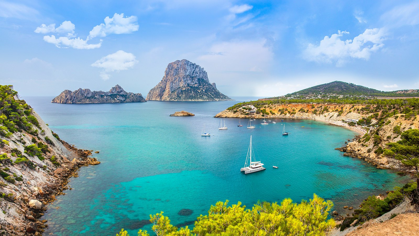 A view of the azure sea of Ibiza Island, with boats anchored in the bay.