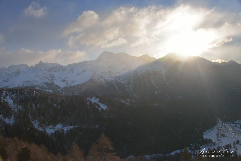 Le soleil passe par dessus les montagnes bordant le Sud-Est du Valposchiavo - Bernina Express -  Voyage Bernard Grua - Rhätische Bahn, Chemins de fer rhétiques