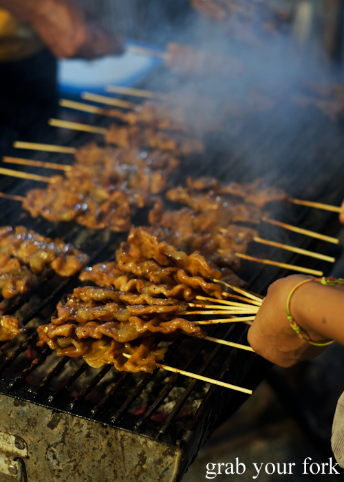 Moo ping grilled pork skewers on charcoal at Build Market in Khao Lak, Thailand