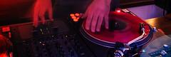 hand of dj on vinyl disk in red light