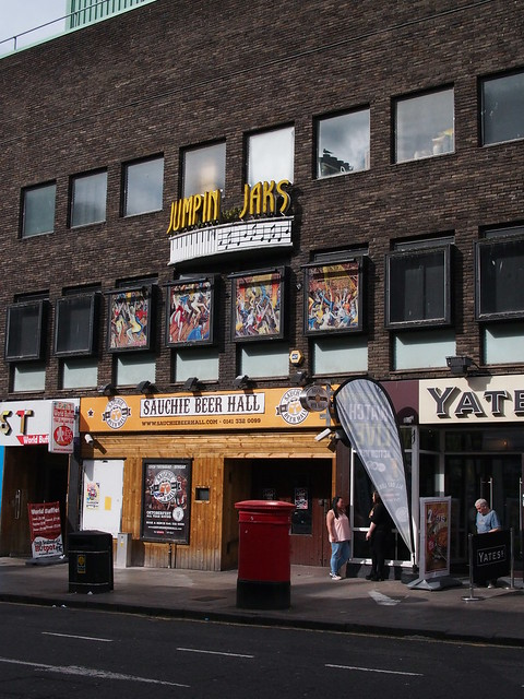 "dark brown brick building with a yellow ""Jumpin' Jaks"" sign up high, and at street level ""Sauchie beer hall"" above a wood panelled store front."