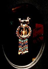 Boucle d'oreille incrustée en or arborant la figurine de Toutânkhamon en cornaline entre deux uraeus : une pièce d'une paire, 1336-1326 av. J.-C.