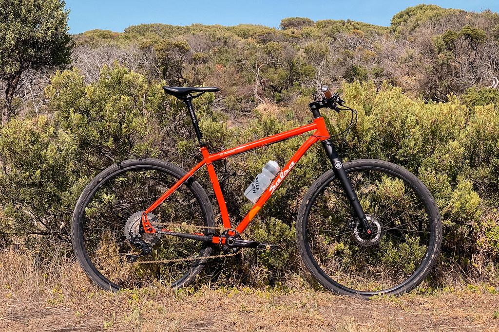 Orange mountain bike against a backdrop of Australian Coastal scrub