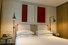 """Double bed with white sheets and brick wall in the hotel room of """"The Corner Hotel"""" near the Plaça del Doctor Letamendi Park in Barcelona, Spain"""