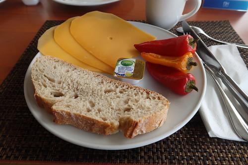 Weißbrot mit Butter, Käsescheiben und heißen Paprikaschoten