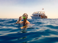 Person with snorkeling mask and a ship in the background