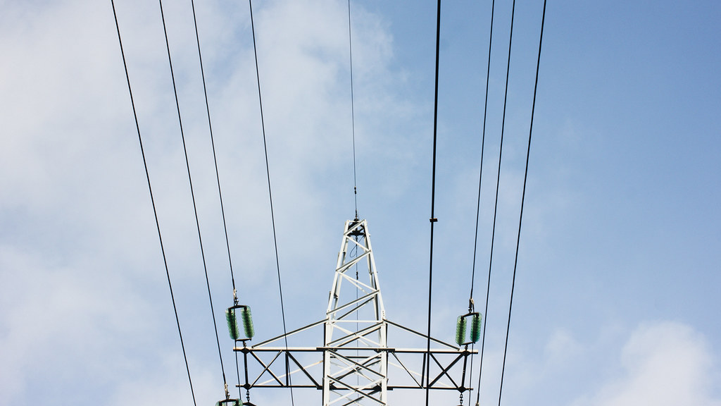 Looking up at an electric pylon and its wires against a blue sky