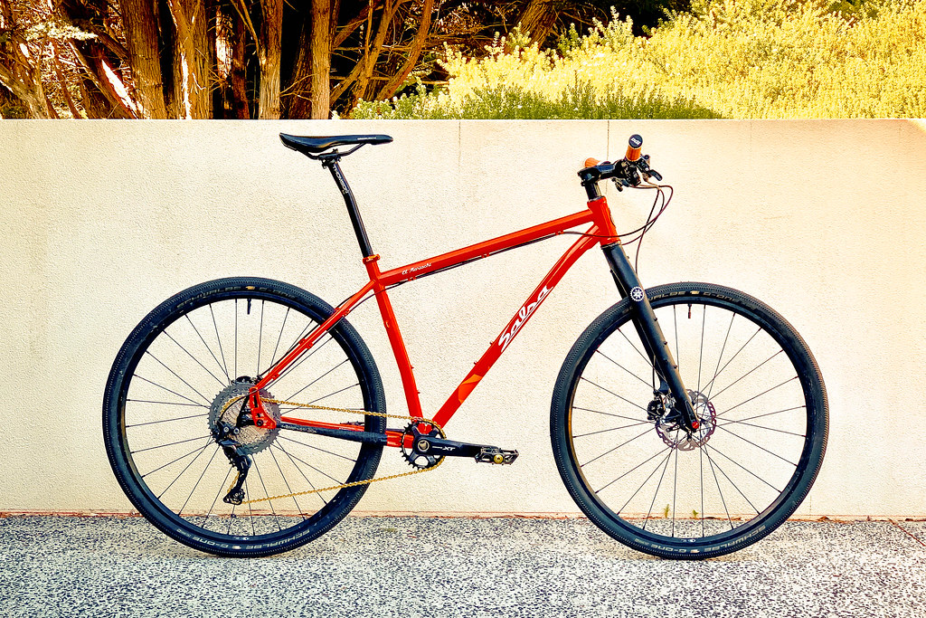 Orange mountain bike against a plain white wall