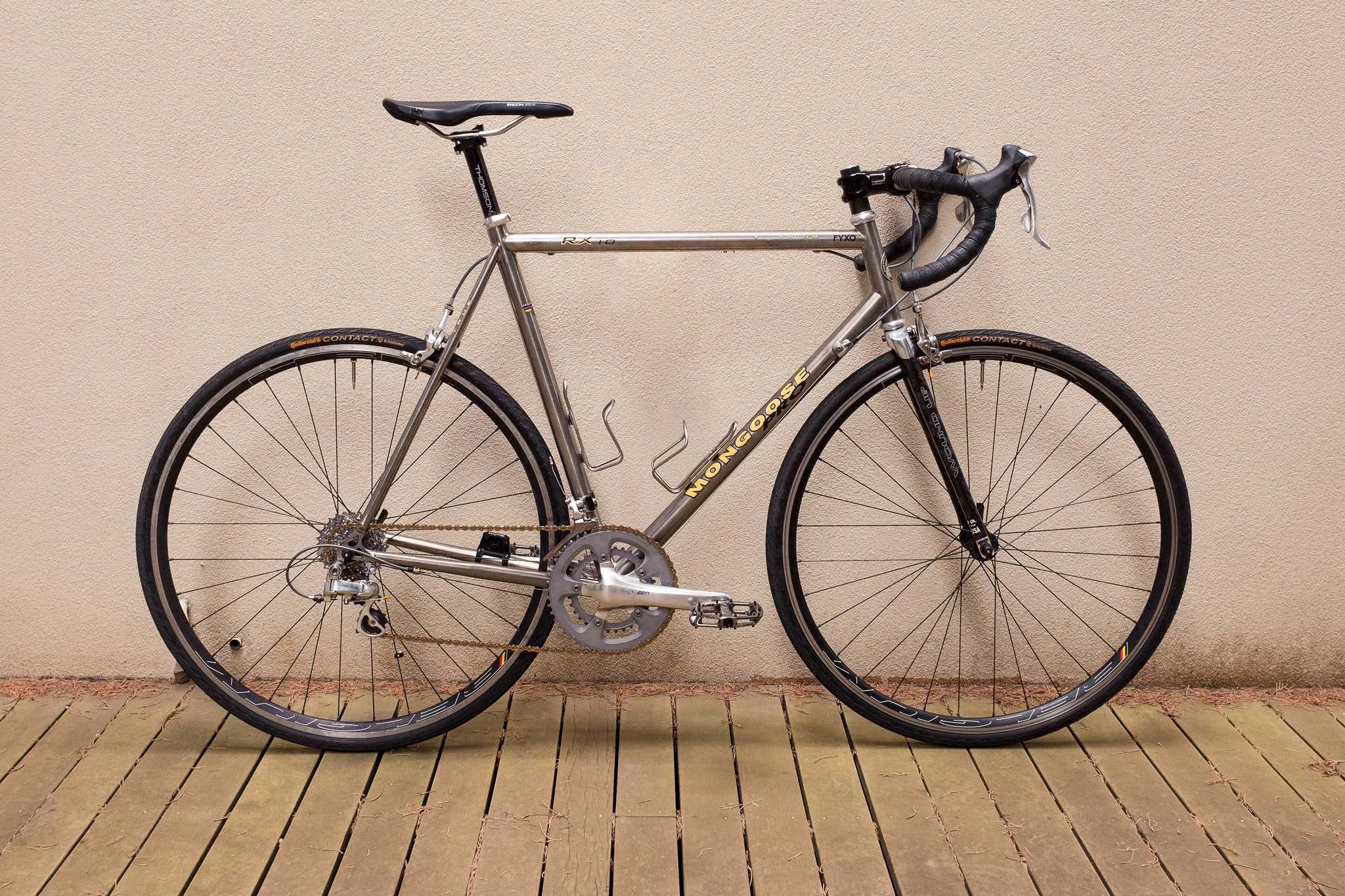 Drive-side view of vintage titanium Mongoose road bike leaning against a wall