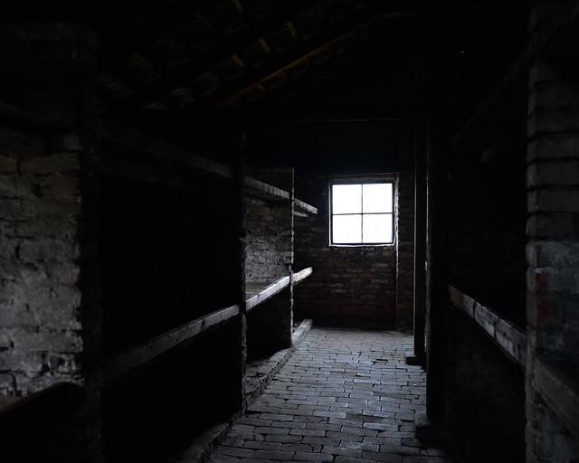 Lúgruve interior a oscuras de uno de los barracones de Auschwitz